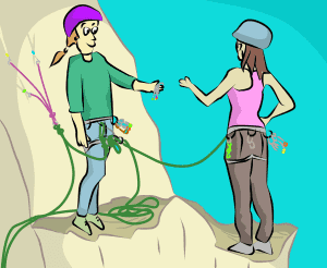 Rock climbers swapping gear at belay anchor